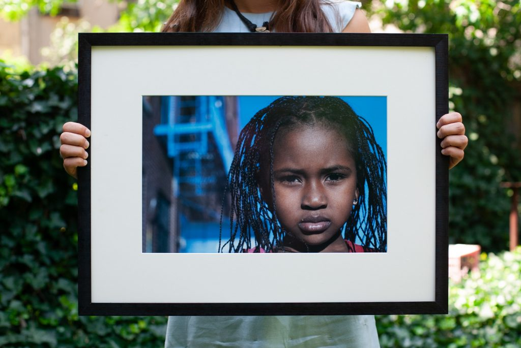 Hands of a woman holds a framed photo of a girl from Sierra Leone.