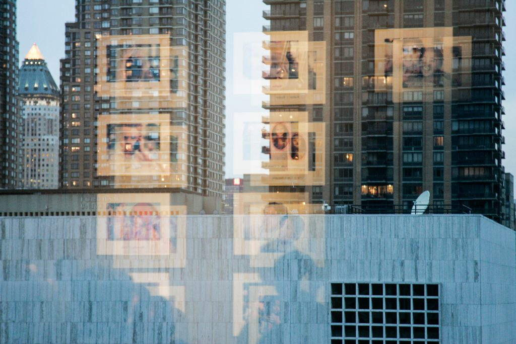 Reflection of a grid of photogrpahs exhibited at Lincoln Center in New York City.