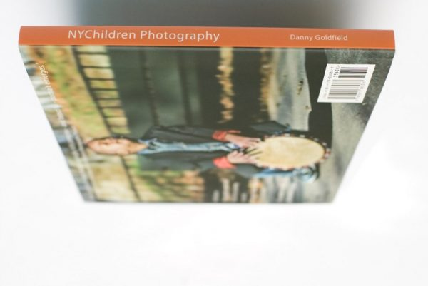 NYChildren Photography Book by Danny Goldfield features a young boy playing a Djembe drum  on the back cover with his eyes closed, lost in his music.