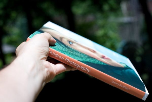 NYChildren Photography Book by Danny Goldfield is extendout in someone's hand, wanting to gift it away to some one special.