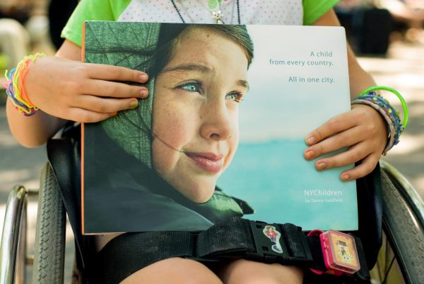 NYChildren Photography Book by Danny Goldfield in the hands of a girl with multi colored bracelettes and nail polish.